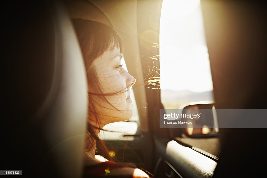 Woman with hair blowing looking out window of car at desert landscape