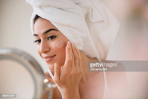 woman with hair in towel rubbing lotion on face - aplicando - fotografias e filmes do acervo