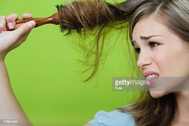Woman with Hair Tangled in Hair Brush