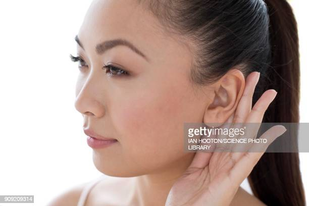 Woman with hand behind ear
