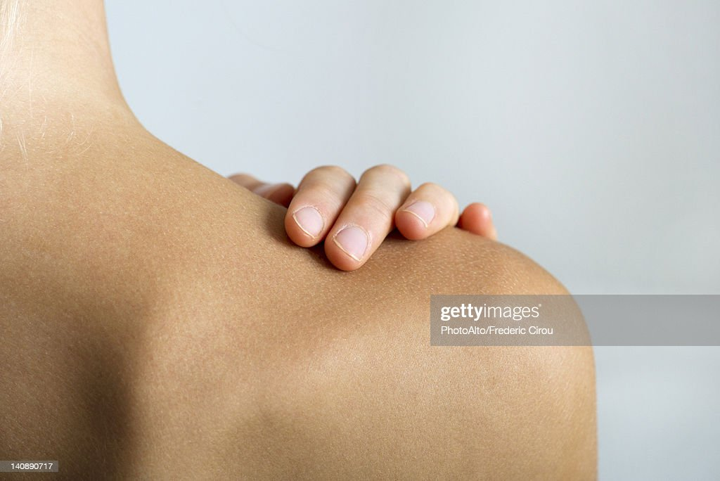 Woman with hand on bare shoulder, close-up : Stock Photo