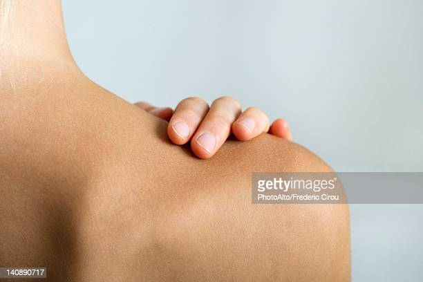 woman with hand on bare shoulder, close-up - human skin stock pictures, royalty-free photos & images