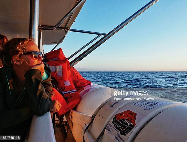 Woman With Hand On Chin Looking At Sea From Boat Sailing In Sea