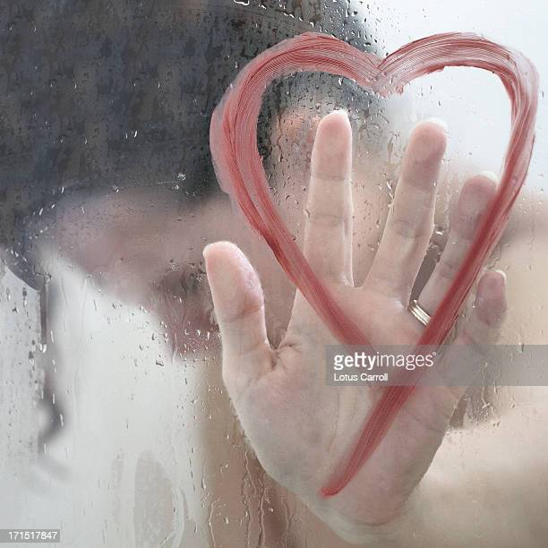 Woman with hand on heart shape on shower door