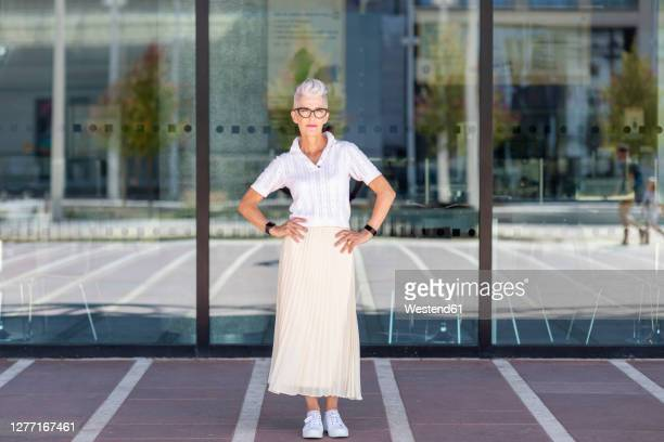 woman with hand on hip standing against glass window in city - one senior woman only stock pictures, royalty-free photos & images