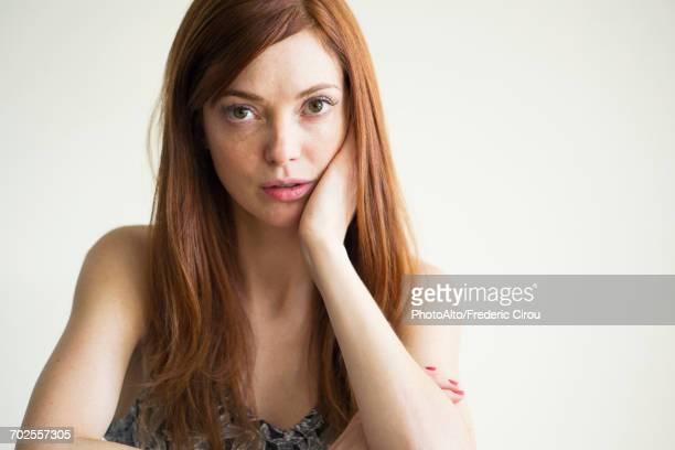 woman with hand under chin, portrait - femme bouder photos et images de collection