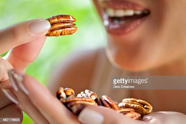 Woman with handful of pecans