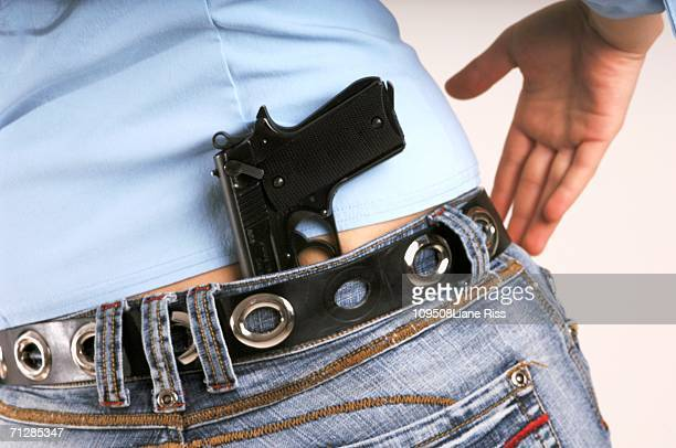 Woman with handgun in jeans, mid-section, close-up