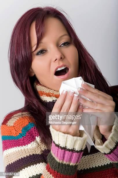 Woman with handkerchief sneezing
