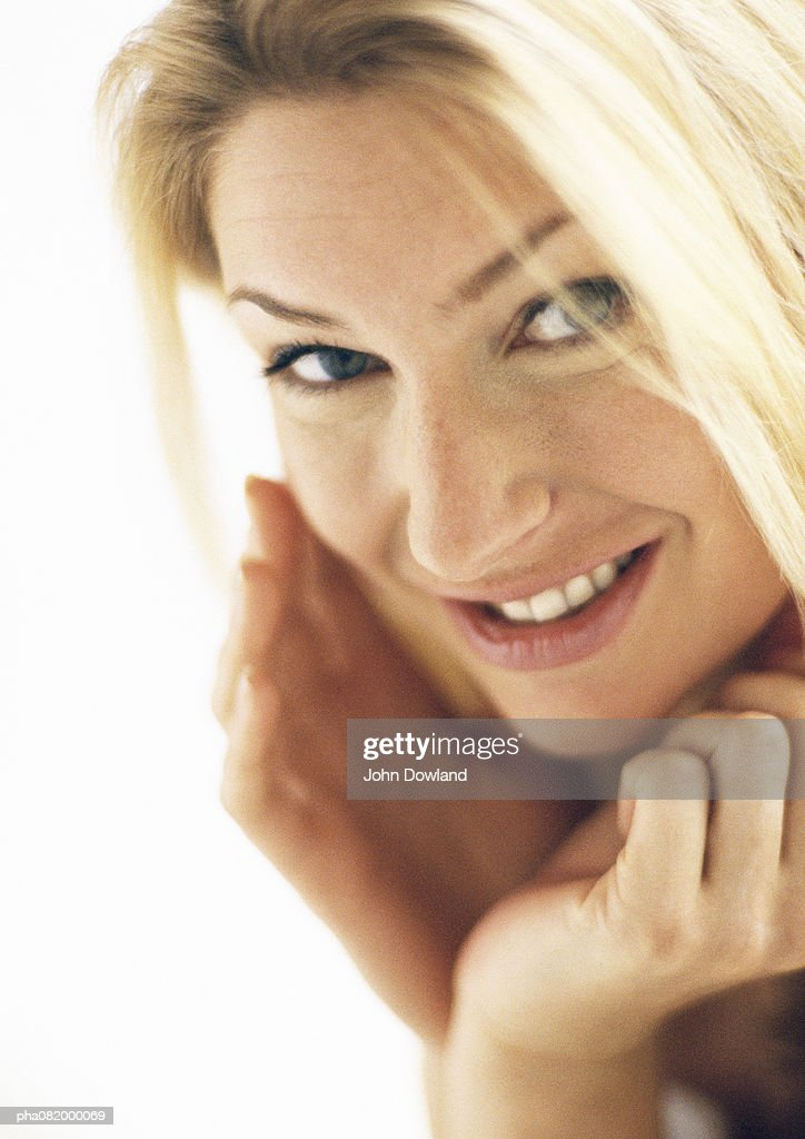 Woman with hands around face, looking at camera, portrait. : Stockfoto
