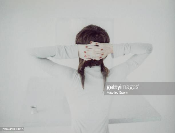 Woman with hands behind head, rear view