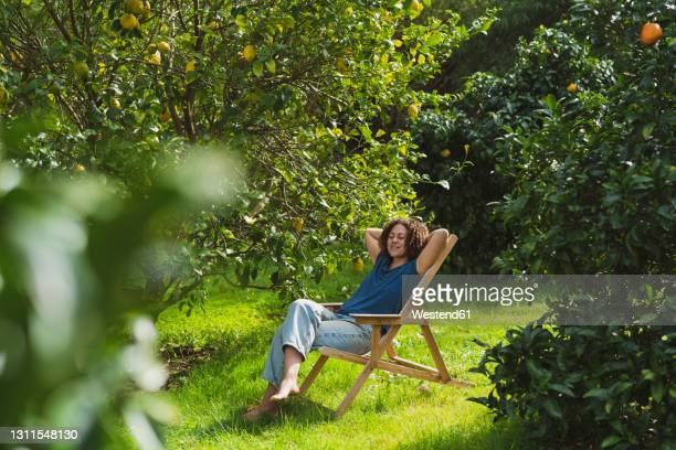 woman with hands behind head relaxing on chair amidst trees in garden - albero da frutto foto e immagini stock