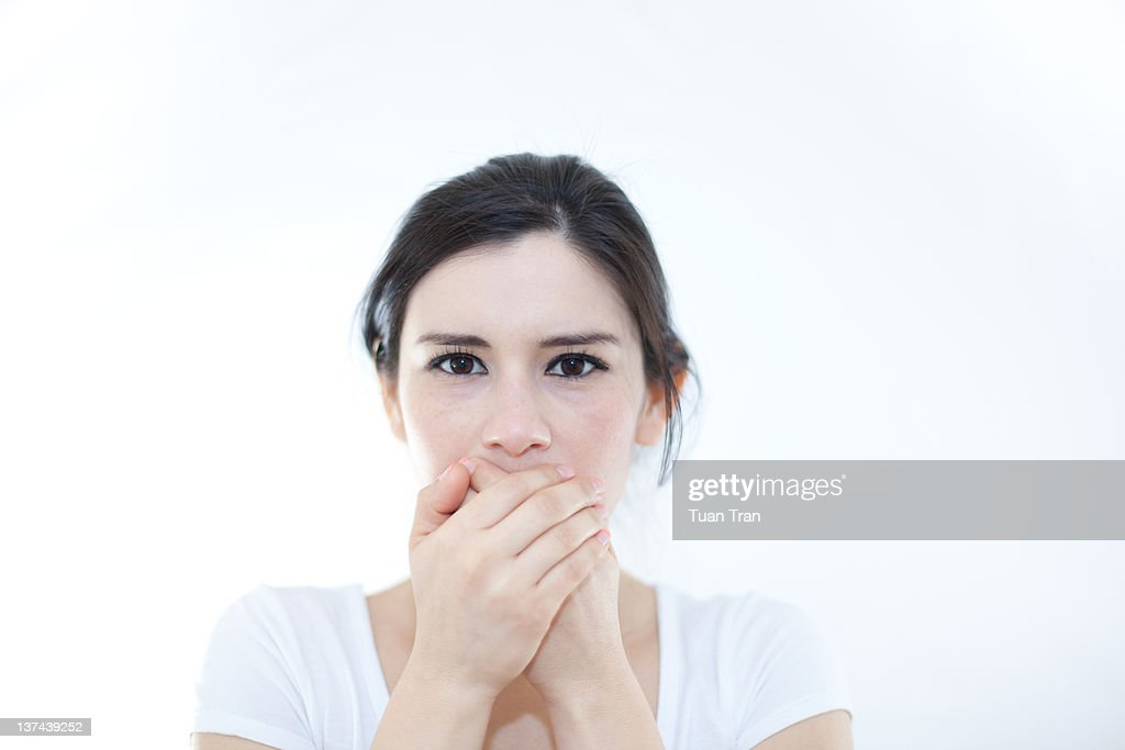 Woman with hands covering over her mouth : Stock Photo