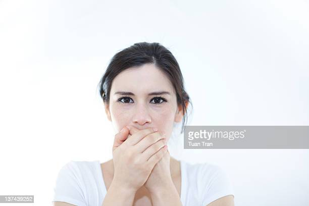 Woman with hands covering over her mouth