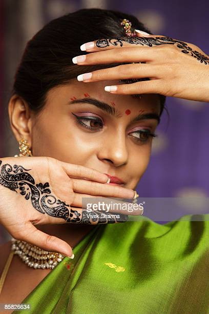 woman with hands decorated in henna