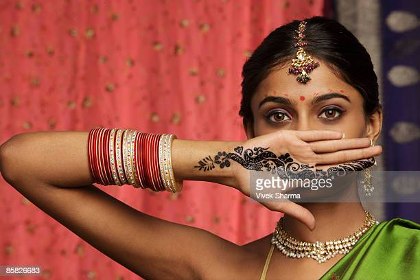 woman with hands decorated in henna, standing against wall of sari fabric