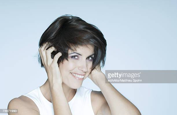 Woman with hands in hair, smiling, portrait