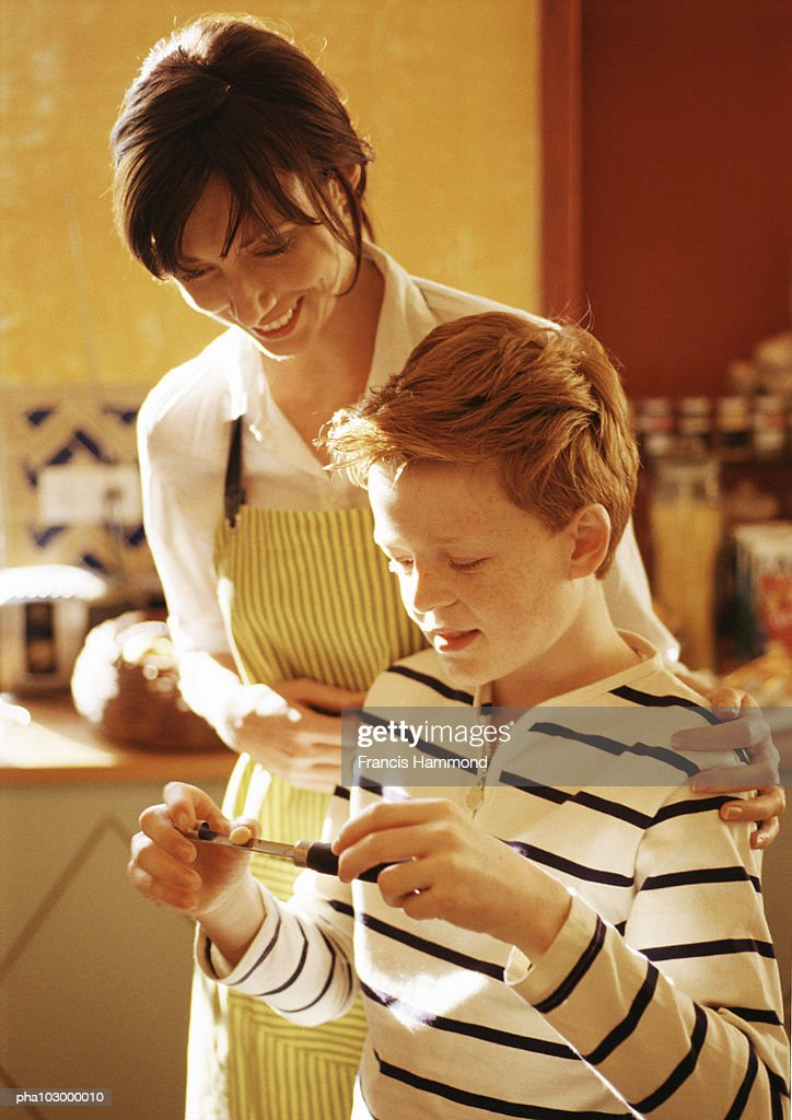 Woman with hands on child's shoulder, smiling : Stockfoto