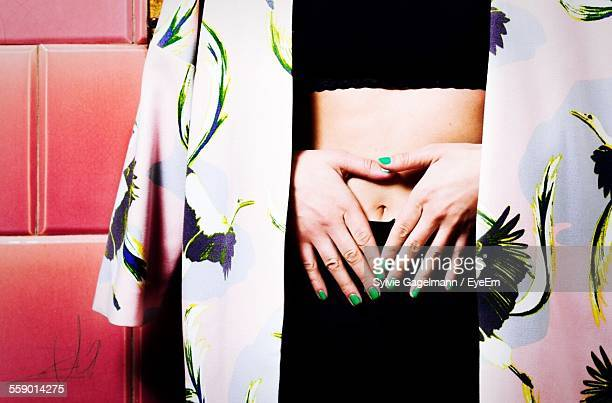woman with hands on stomach - menstruation stock pictures, royalty-free photos & images
