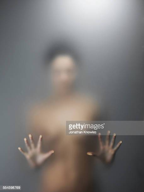 Woman with hands pressed against frosted glass