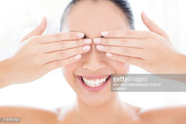 Woman with hands touching covering eyes