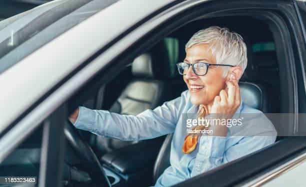 woman with hands-free in the car - motorista ocupação imagens e fotografias de stock