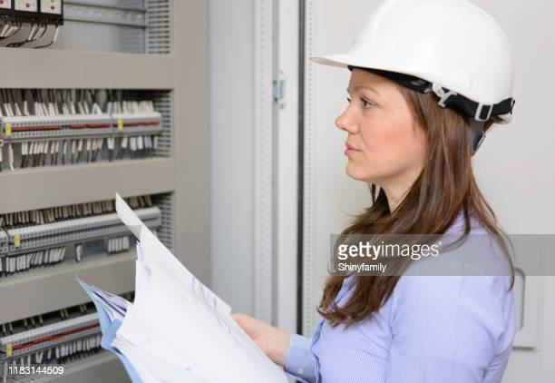 woman with hardhat looking at blueprints in power substation. - generator stock pictures, royalty-free photos & images
