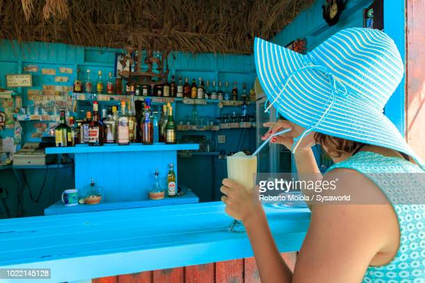 Woman with hat and charming dress drinks a fresh fruit cocktail at the beach bar, Long Bay, Antigua