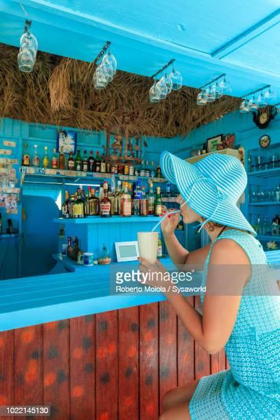 woman with hat and charming dress drinks a fresh fruit cocktail at the beach bar, long bay, antigua - isla de antigua fotografías e imágenes de stock