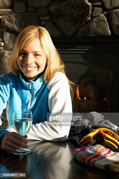 Woman with hat and gloves drinking wine beside fireplace, portrait