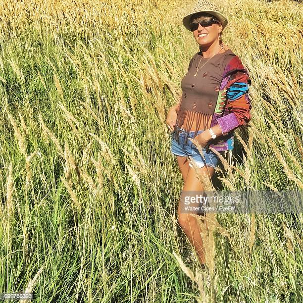 woman with hat and hands in pockets standing on field during sunny day - walter ciceri foto e immagini stock