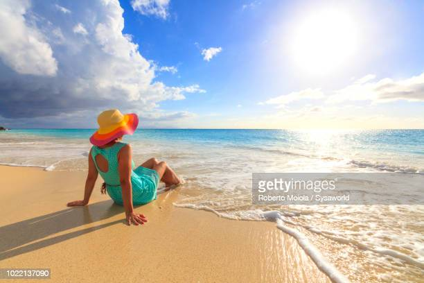 woman with hat and turquoise dress sittes on seashore looking at turquoise caribbean sea, ffryes beach, antigua - caribbean stock pictures, royalty-free photos & images