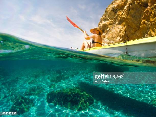 Woman with hat doing kayak taking picture from underwater view exploring the natural Medes islands in the shoreline of Costa Brava Mediterranean Sea during summer vacations in a paradise place with creative point of view.