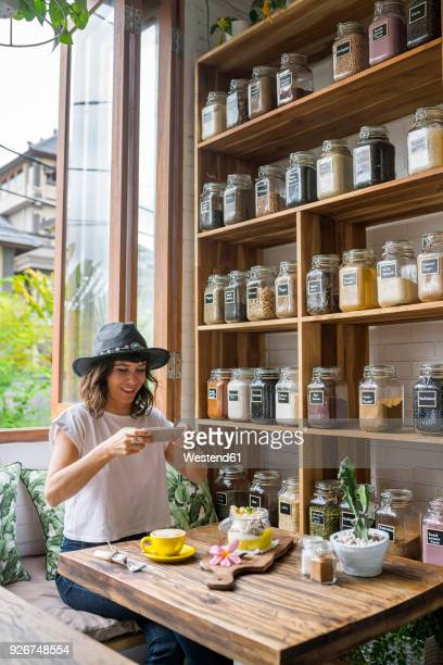 woman with hat in a cafe taking picture of food with smartphone - fotografische thema's stockfoto's en -beelden