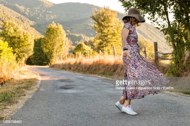 woman with hat on road amidst trees - long dress stock pictures, royalty-free photos & images
