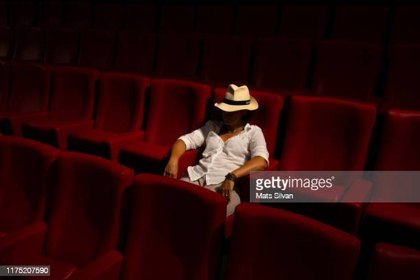 woman with hat sitting alone in a movie theater - film screening stock pictures, royalty-free photos & images