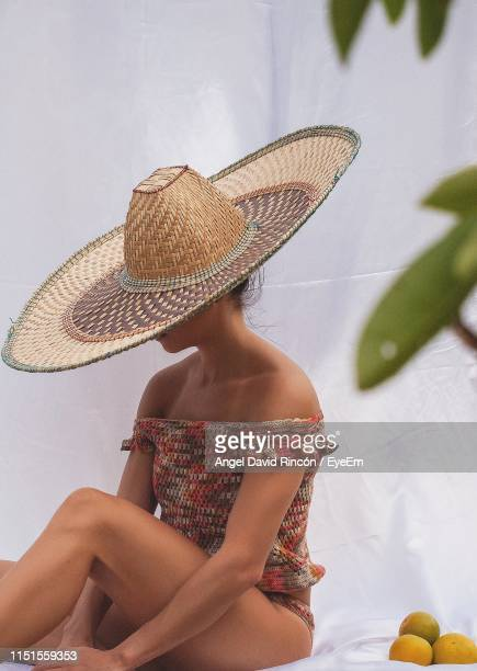 woman with hat sitting on bed by fruits - straw hat stock pictures, royalty-free photos & images