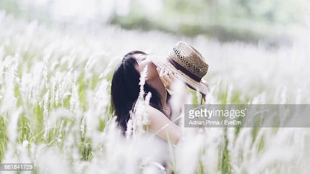 Woman With Hat Sitting On Field