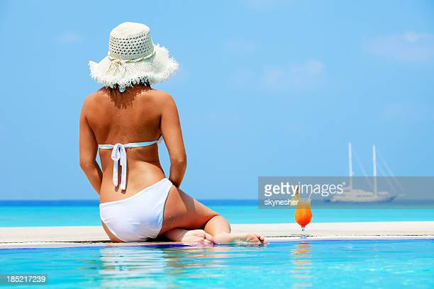 Woman with hat sitting on the swimming pool.