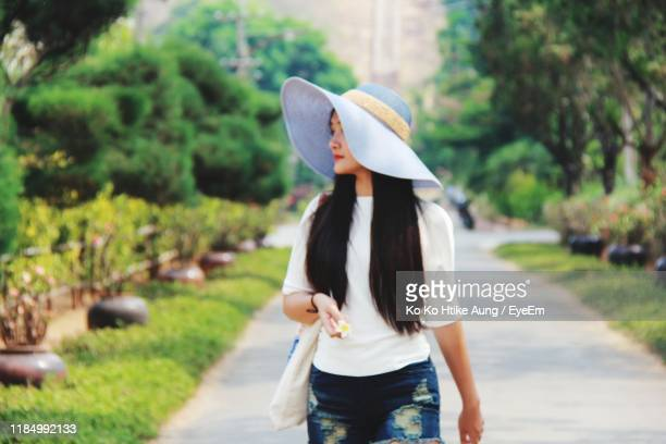 woman with hat walking on footpath in park - ko ko htike aung stock pictures, royalty-free photos & images