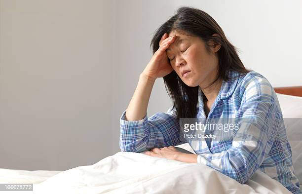 woman with head ache in bed - exhaustion stock pictures, royalty-free photos & images
