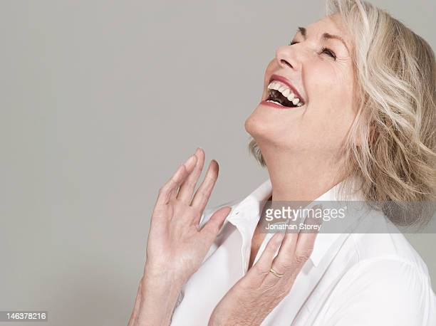 woman with head back laughing, hands clapping