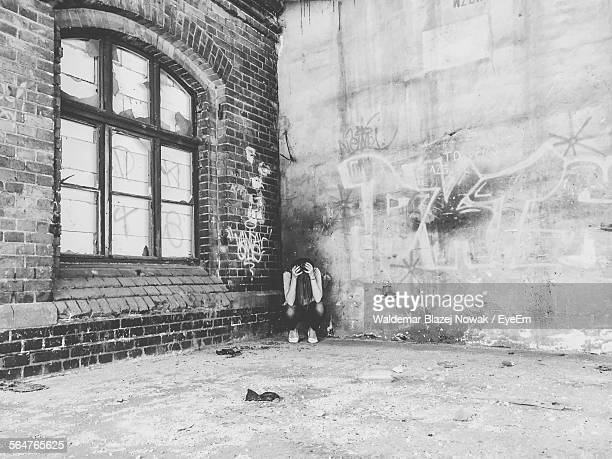 Woman With Head In Hands At Abandoned House