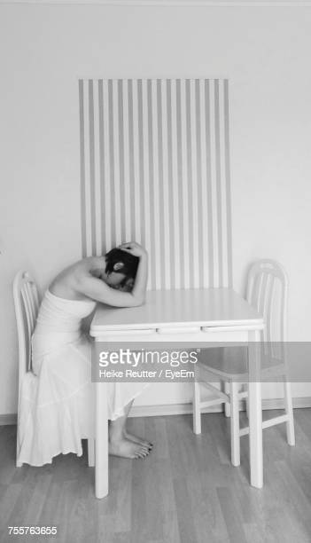 woman with head in hands sitting on chair at home - vestido a rayas fotografías e imágenes de stock