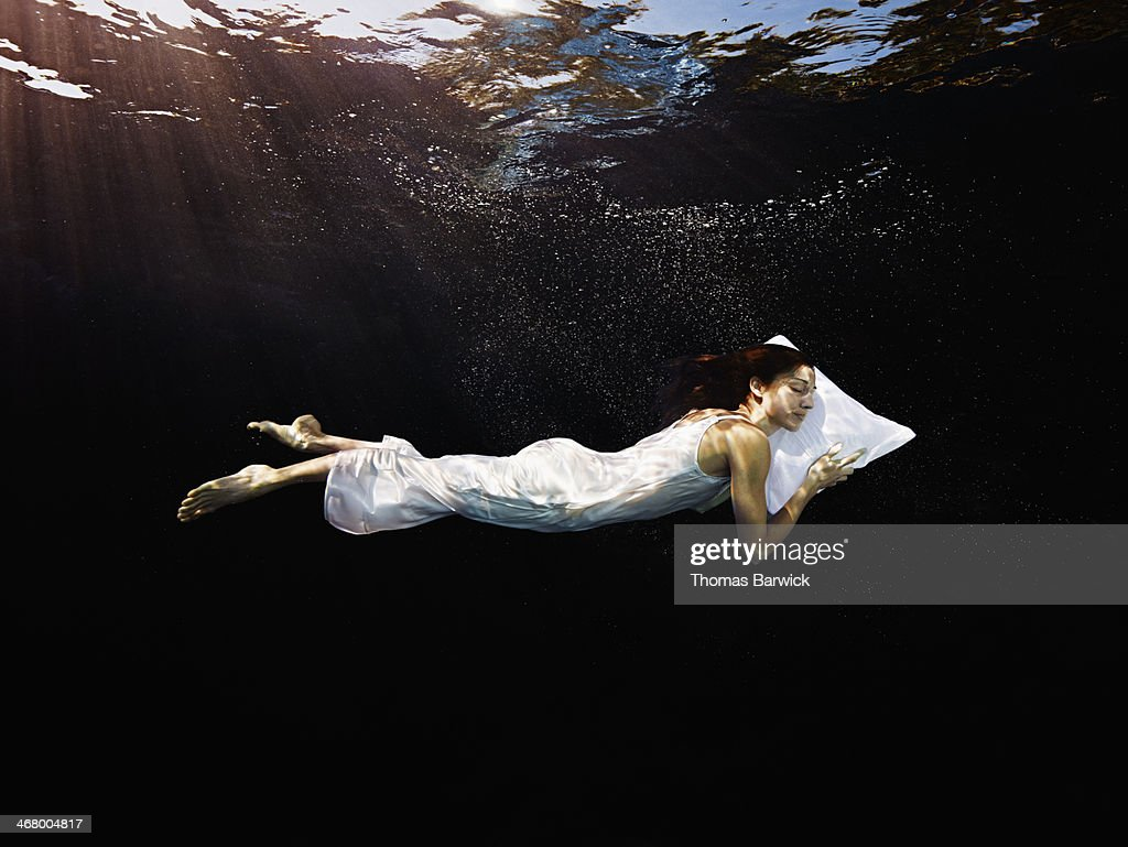 Woman with head on pillow sleeping underwater : Stock Photo