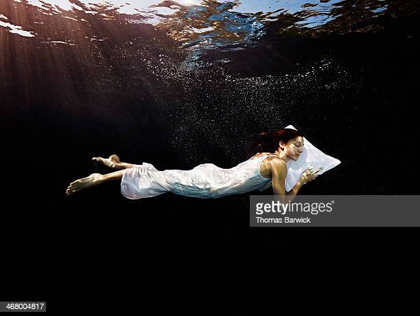 woman with head on pillow sleeping underwater - une seule femme d'âge moyen photos et images de collection
