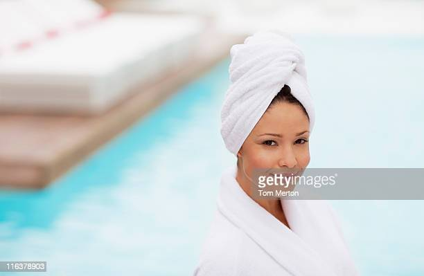 Femme avec tête enveloppé dans une serviette au bord de la piscine