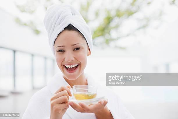 Femme avec tête enveloppé dans une serviette boire du thé