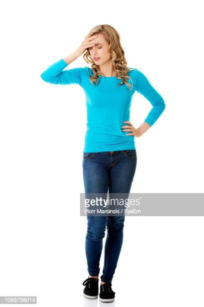 Woman With Headache Standing Against White Background