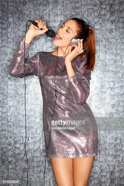mujer con auriculares y micrófono de música karaoke en club nocturno - una sola mujer joven fotografías e imágenes de stock